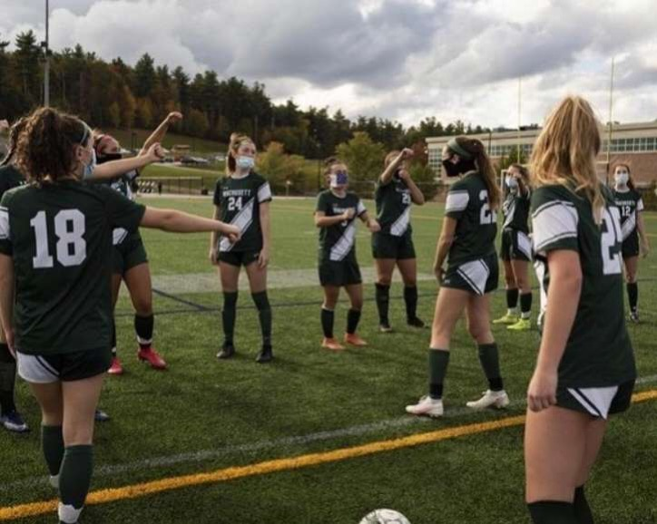 Girl's varsity soccer team stretches before a game.
