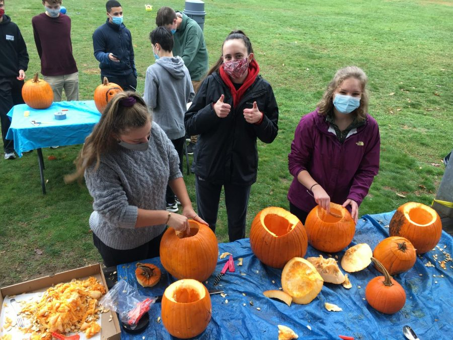 Seniors Abby Tasca (left), Leah Michalowski (middle), and Annabelle Havens (right) carving pumpkins for DECA.