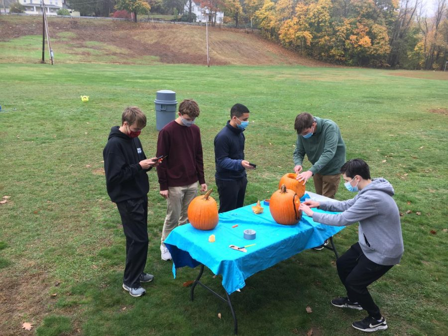 (From left to right) seniors Jake Williams, Satchel Moore, Evan Appel, Alden Waterhouse, and junior Kyle Burque carving pumpkins for DECA.